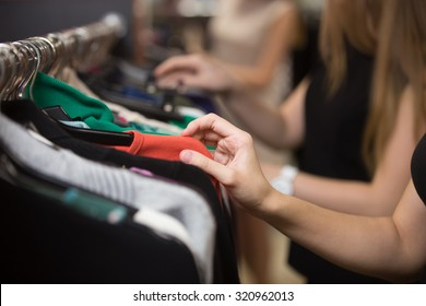 Young beautiful women shopping in fashion mall, choosing new clothes, looking through hangers with different casual colorful garments on hangers, close up of hands