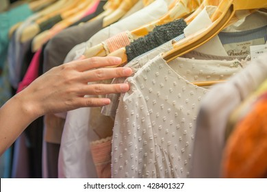 Young beautiful women shopping in fashion mall, choosing new clothes