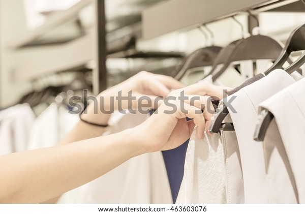 ファッションモールで買い物をする若い美しい女性、新しい服を選ぶ、さまざまなカラフルな衣服を着たハンガーを通してハンガーを見る、手の接写