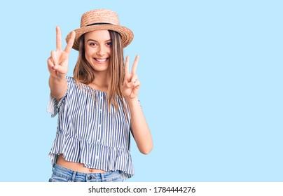 Jóvenes hermosas mujeres con sombrero y camiseta sonriendo frente a la cámara mostrando dedos haciendo señas de victoria. número dos.