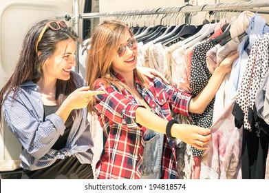 Young beautiful women at weekly cloth market - Best friends sharing free time having fun and shopping in the old town in a sunny day