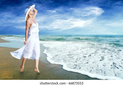 Young beautiful women in the white on the sunny tropical beach