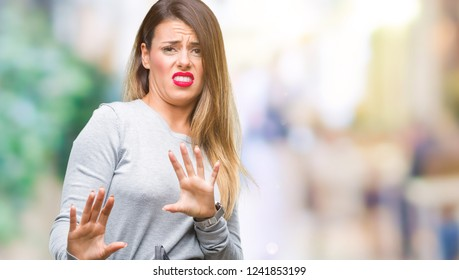 Young beautiful worker business woman over isolated background disgusted expression, displeased and fearful doing disgust face because aversion reaction. With hands raised. Annoying concept.