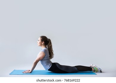 Young beautiful yoga posing on gray background. Yoga, fitness and training.