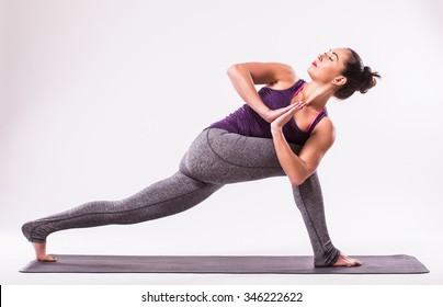 young beautiful yoga woman posing on a studio background