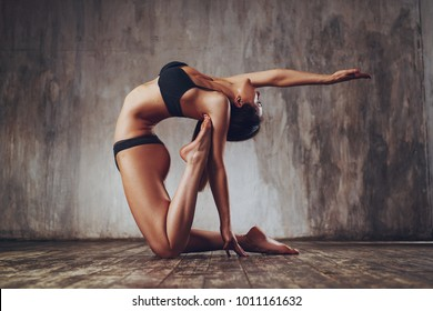 Young beautiful yogi woman stretching on wall background