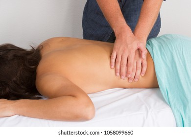 Young beautifulCaucasian woman taking massage procedure from a pro masseur in a hotel spa