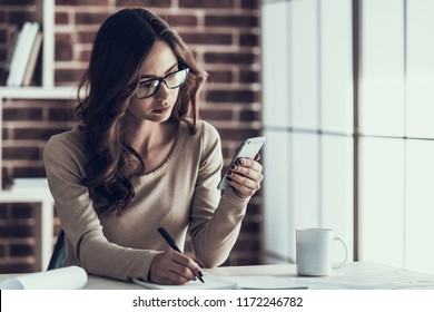 Young Beautifull Business Woman making Notes. Beautiful Woman wearing Glasses Sitting at Desk looking at Smartphone and taking Notes using Notebook. Businesswoman Working Remotely at Home