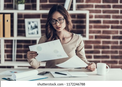 Young Beautifull Woman Upset with Paperwork. Beautiful Woman wearing Glasses Sitting at Desk and holding Papers with Diagrams. Businesswoman Working Remotely at Home. Homeoffice Concept