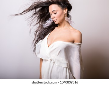 Young beautifull woman in white dress studio portrait.