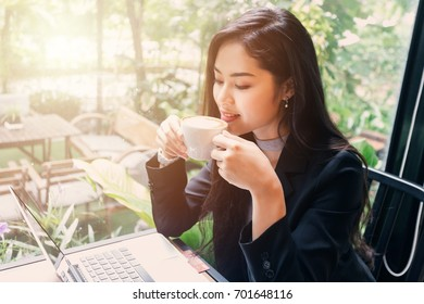 Young beauty Asian business woman with laptop smart phone and coffee on table in working space.
