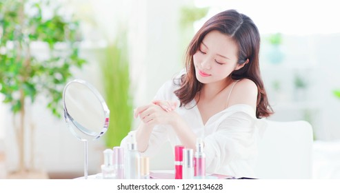 Young beauty asian woman applying hand cream at home