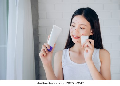 Young Beauty Asian Woman Cleaning Face with Cotton and Cleansing foam Skincare for Reduce acne problems Her Smile and Happy Morning in White Bedroom.