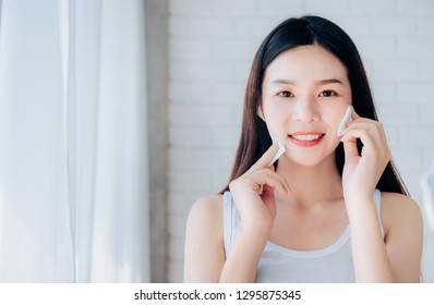 Young Beauty Asian Woman Cleaning Face with Cotton Clear Face Skincare and Smile Morning in White Bedroom,Copy Space.