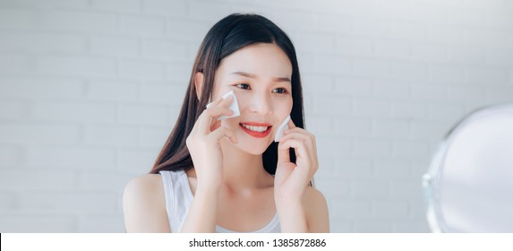 Young Beauty Asian Woman Cleaning Face with Cotton Clear Face Skincare,Makeup Mirror and Smile Morning in White Bedroom.