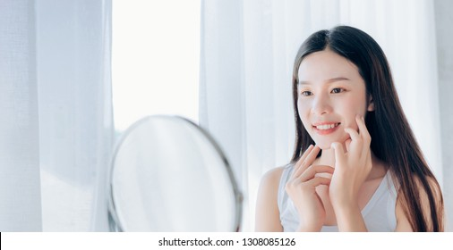 Young Beauty Asian Woman Looking at Mirror Check Clear Face Skincare and Smile Morning in White Bedroom, Crop for Web Banner Panoramic.