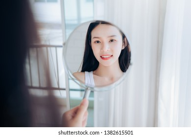 Young Beauty Asian Woman Looking at Mirror Check Clear Face Skincare and Smile Morning in White Bedroom.