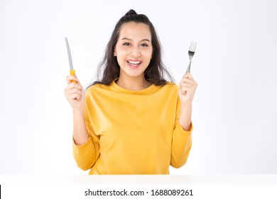 Young beauty Asian woman showing Knife Fork prepare to eat food and she wearing a yellow sweater shot isolated on white background