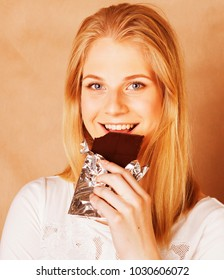 young beauty blond teenage girl eating chocolate smiling