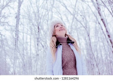 young beauty blond woman stying a snow forest and smiyling, wairing brown sweater, hat and white jacket