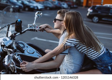 Young beauty caucasian couple in love driving a motorbike together on a highway, hugging and smiling in summer