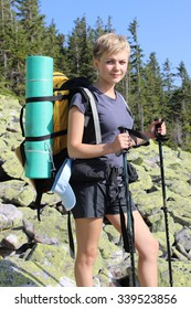 Young beauty female hiker with backpack in mountains