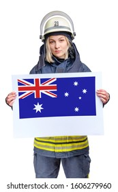 young beauty firefighter wearing uniform and helmet looking to the camera and holding paper sheet with australian flag in hands. isolated on white background.