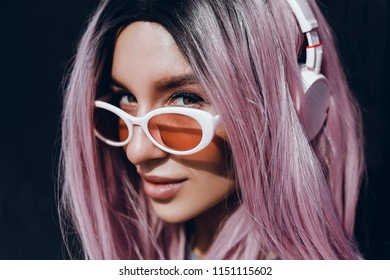 Young beauty girl jumping on the street, outdoor fashion portrait, purple hair, orange sunglasses, shoes, listening music on headphones and using smartphone. Hand up, happy face, smile, crazy