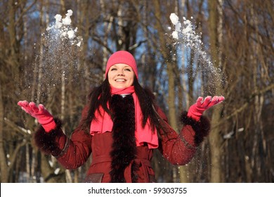 young beauty girl in pink scarf and hat smiling throwing up snow, outdoor at winter day