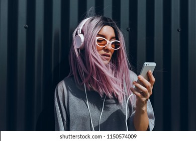 Young beauty girl purple hair make selfie on smartphone, happy face, outdoor hipster portrait on the street, smile happy face, listen music on headphones, Amsterdam street, dance, player,photo concept