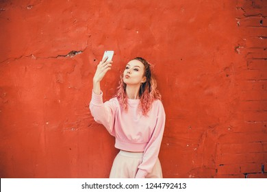 Young beauty girl purple hair make selfie on smartphone, happy face, outdoor hipster portrait on the street, smile happy face, pink color, crazy emotion,Amsterdam street, dance, player,photo concept