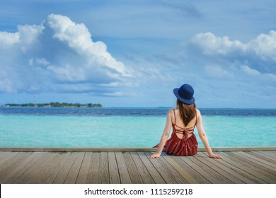 Young beauty lady with red dress and blue hat sit on the pier look over sea and blue sky