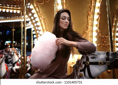 Young beauty model woman posing with old horse carousel in summer park with magic lights