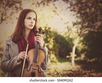 Young beauty musician holding his violin, urban female portrait