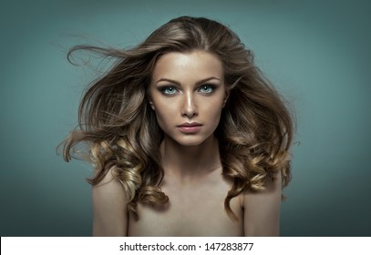Young beauty with perfect make up and hair fluttering in the wind