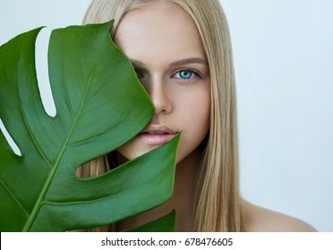 Young beauty smiling blonde model with natural make up and green leaf. Spa and wellness. Youth, teens and skin care concept.  Close up, selective focus.