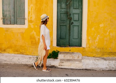 Young beauty tourist woman goes along street in an old Greek town. Greece. Sightseeing in Kefalonia. Travel and vacation concept.