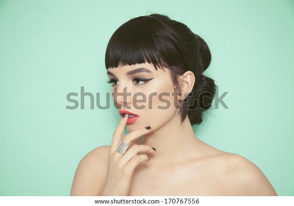 Young beauty woman with fringe, black nails and big silver ring touching her lips. Green background.