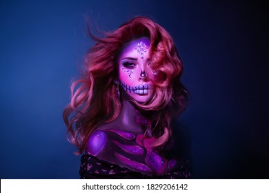 A young beauty woman with long hair in the image of a sugar skull. Hair flying in wind. Halloween carnival party. Close up portrait. A cute sad face in neon colored light