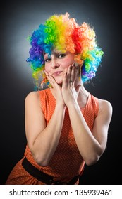 young beauty woman in multicolored clown wig smiling on black background