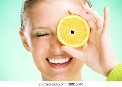 young beauty woman with orange on green background