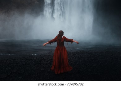 Young beauty woman over nature waterfall background in Iceland. Mysterious girl in a long red dress watch Skogafoss waterfall in the Iceland.