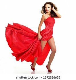 Young beauty woman in red waving flying  dress. Dancer in silk dress. high heel shoes