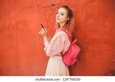 Young beauty woman using smartphone in hand, street photo, outdoor hipster portrait, fashion model, cell phone, text message, video content, pink hair and backpack, isolated, wall red, Amsterdam