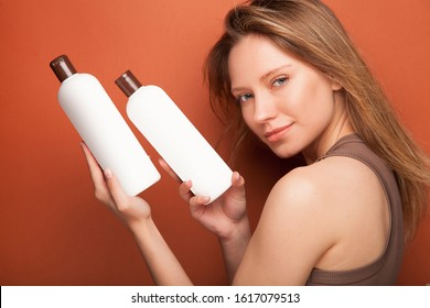 Young beautyful woman holding two bottles of shampoo and conditioner. Photo in studio