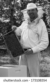 Young beekeeper smiling and showing his bee colony