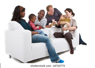 Young befriended multiracial families sitting on the couch and playing with their kids.