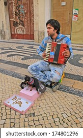 Young beggar musician with small cute dog play accordion and ask for money on street of Lisbon, Portugal on November, 2013.