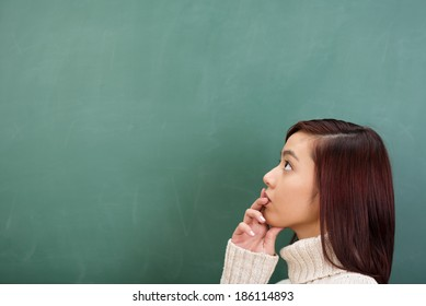 Young bemused Asian student seeking an answer staring at a blank green chalkboard with her hand to her lips and a bewildered expression