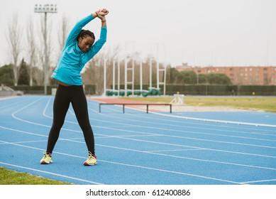 Young bent woman training on the stadium. Horizontal outdoors shot.